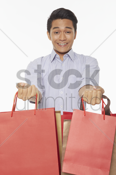 man smiling and carrying shopping bags stock photo