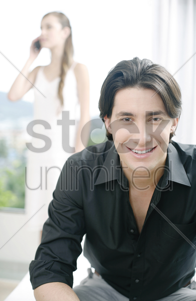 man smiling at the camera with his girlfriend talking on the phone in the background stock photo
