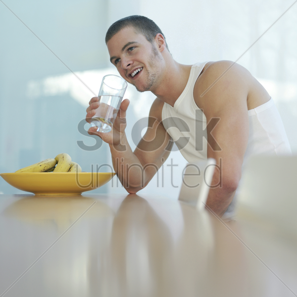 man smiling while drinking water stock photo