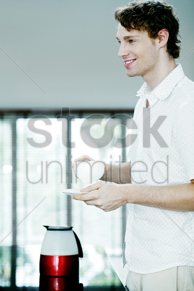 man smiling while holding a cup and a saucer stock photo