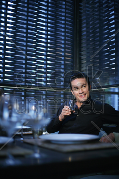 man smiling while holding a glass of wine stock photo