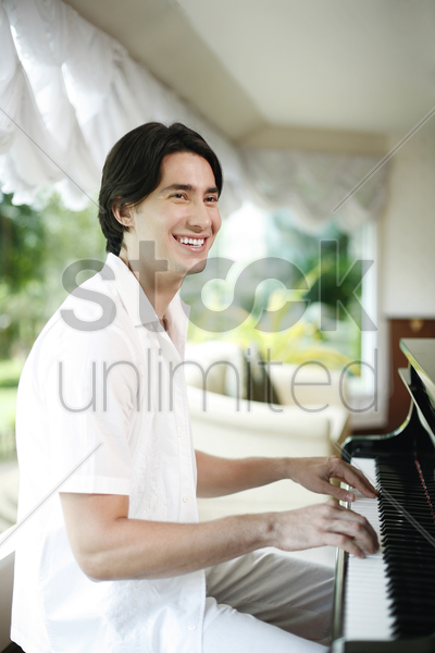 man smiling while playing piano stock photo