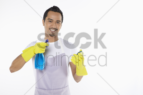 man spraying detergent on a sponge stock photo