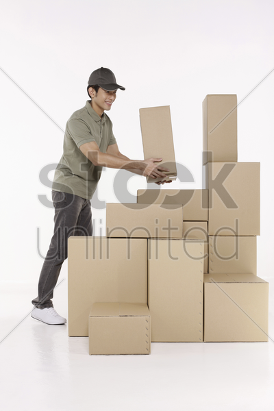 man stacking up packages stock photo