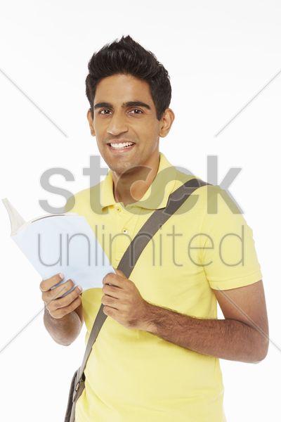 man standing and reading a book stock photo