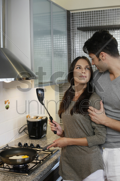man standing behind woman while she is preparing breakfast in kitchen stock photo