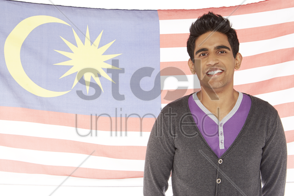 man standing in front of a malaysian flag stock photo