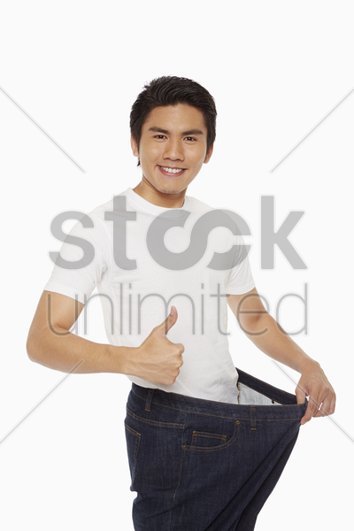 man standing on weight scale, giving thumbs up stock photo