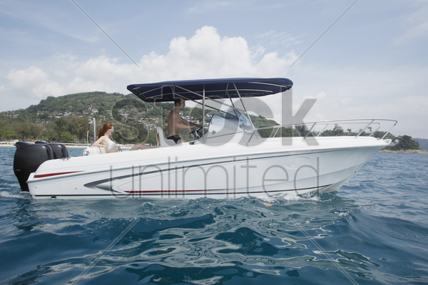 man steering speedboat, woman at the back stock photo