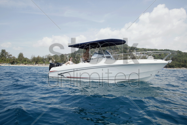 man steering speedboat, woman sitting at the back stock photo