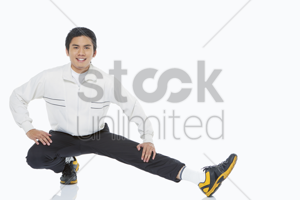 man stretching his left leg stock photo