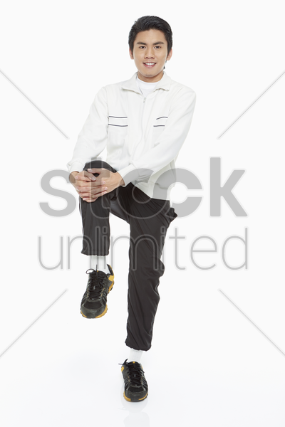 man stretching his right leg stock photo