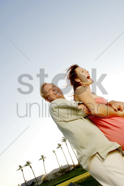 man swinging his wife stock photo