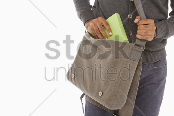 man taking a book out of his bag stock photo