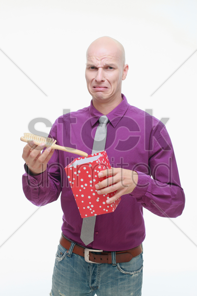 man taking out a hair brush from gift box stock photo