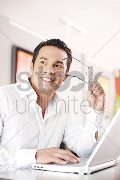 man taking out his glasses while using laptop stock photo