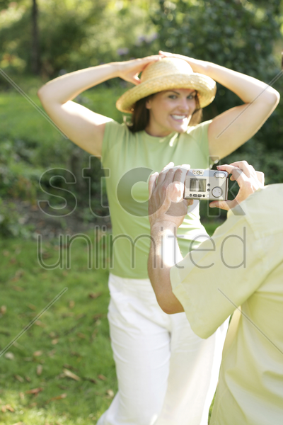 man taking picture for his wife in the park stock photo