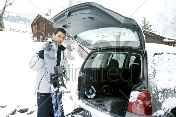 man taking snowboard from his jeep stock photo