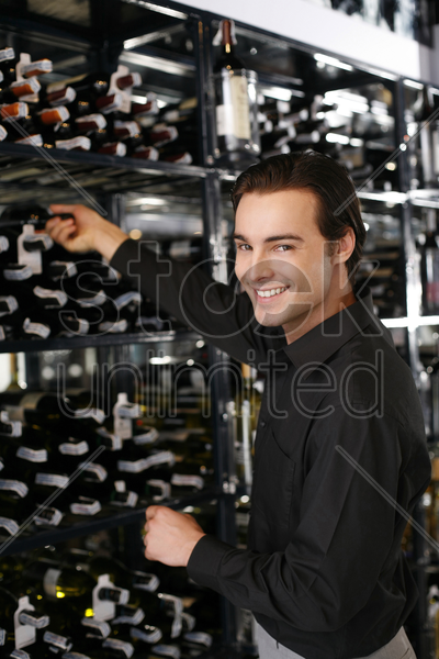 man taking wine bottle from the wine cellar stock photo