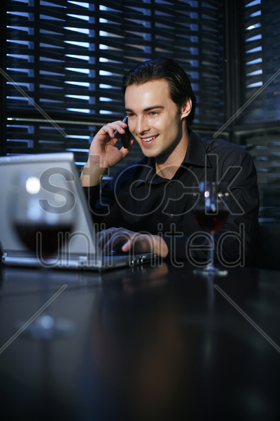 man talking on the mobile phone while using laptop in the restaurant stock photo