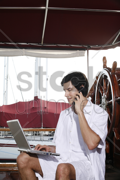 man talking on the mobile phone while using laptop stock photo