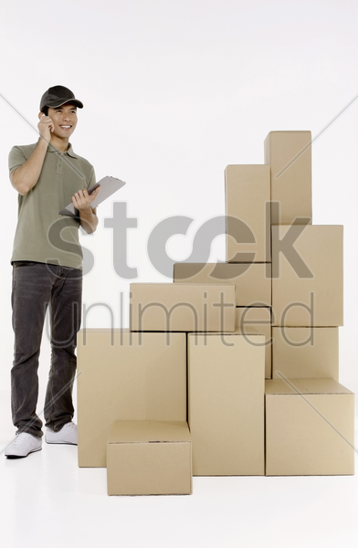 man talking on the phone while checking packages stock photo