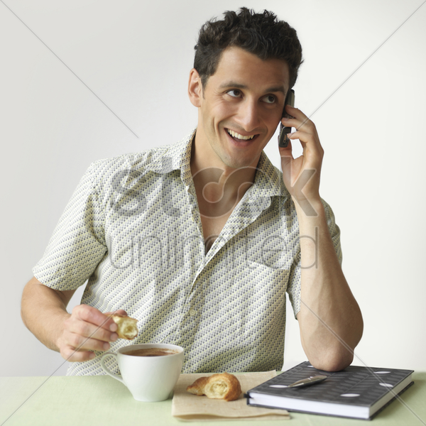 man talking on the phone while having breakfast stock photo