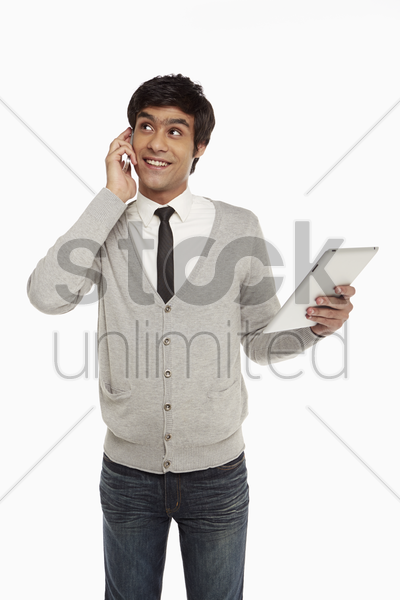 man talking on the phone while looking at digital tablet stock photo