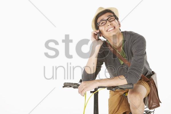man talking on the phone while sitting on the bicycle stock photo
