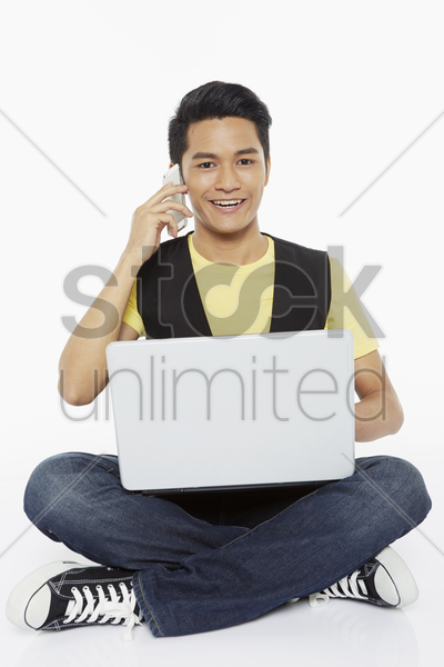 man talking on the phone while using laptop stock photo