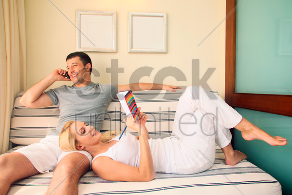 man talking on the phone while woman is lying down on his lap writing in diary stock photo