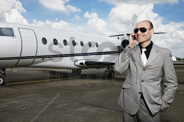 man talking on the phone with private jet in the background stock photo