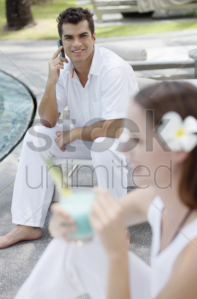 man talking on the phone, woman drinking cocktail stock photo
