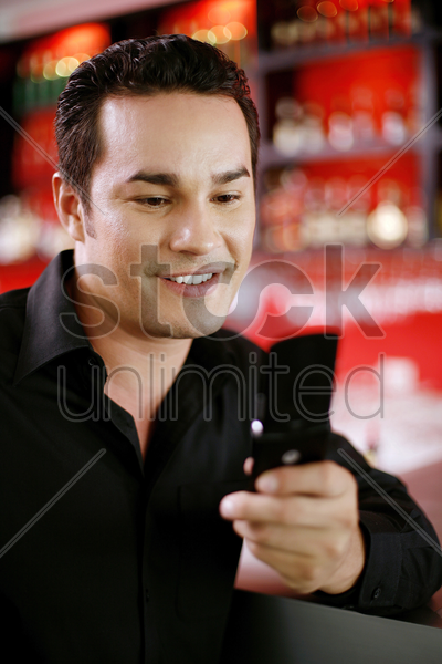 man text messaging on his mobile phone stock photo
