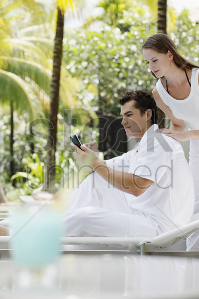 man text messaging on the mobile phone, woman watching from behind stock photo