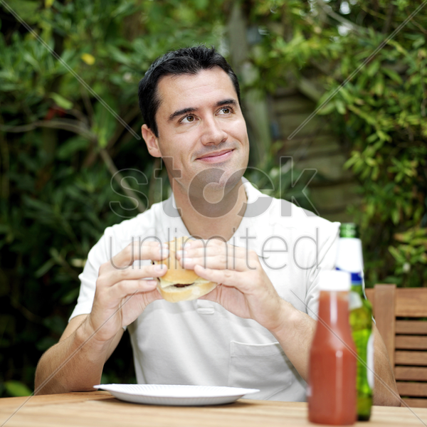 man thinking while holding a burger stock photo