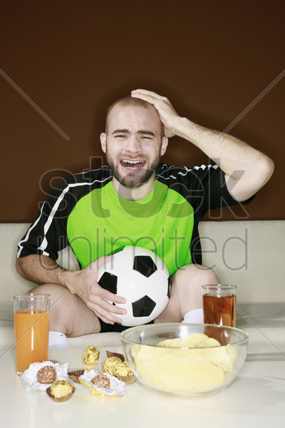 man touching head with disappointment while watching football match at home stock photo