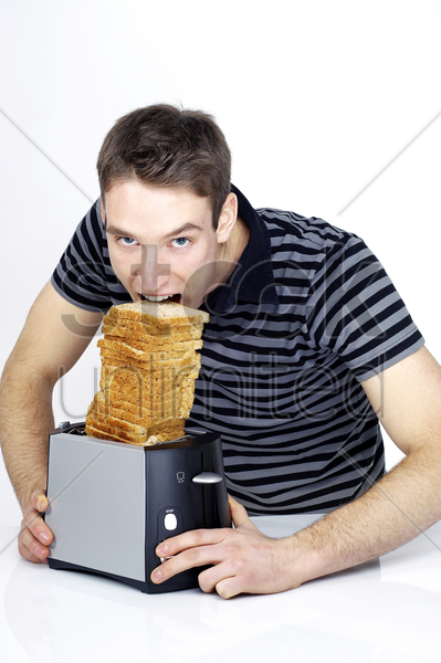 man trying to eat a stack of toasts stock photo