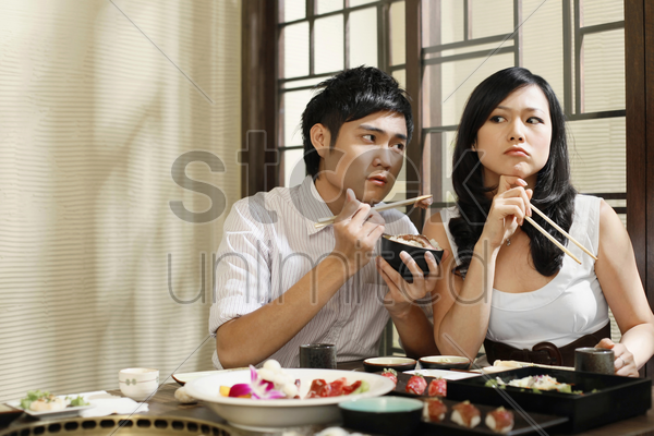 man trying to feed his sulking girlfriend stock photo
