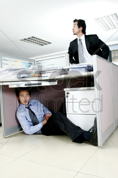 man trying to find his worker who is sleeping under the desk stock photo