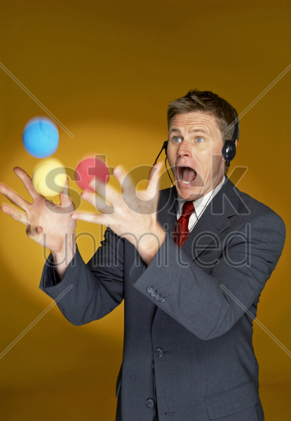man trying to juggle with three balls stock photo