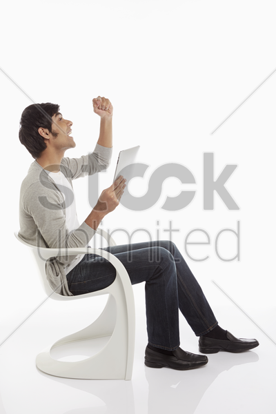 man using a digital tablet, cheering stock photo