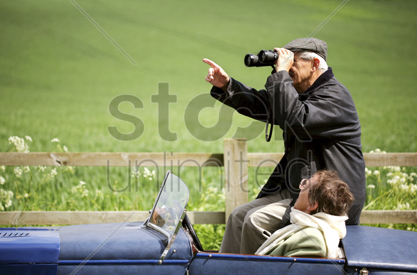 man using binoculars while sitting in the car stock photo