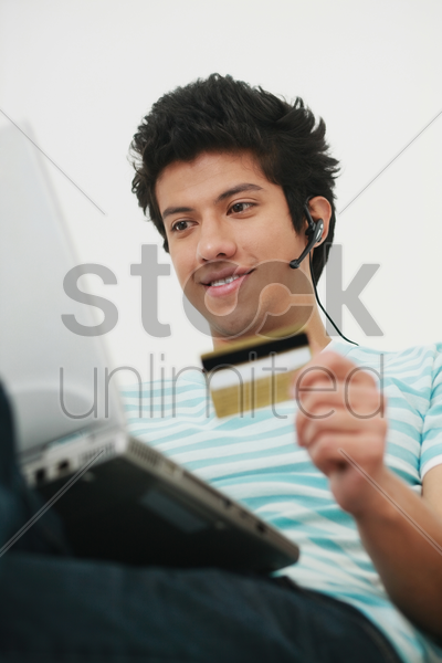 man using laptop and credit card for home shopping stock photo