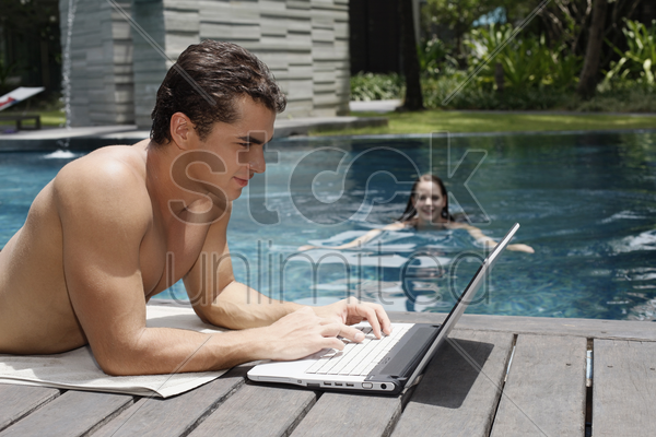 man using laptop by the pool side, woman swimming in the pool stock photo