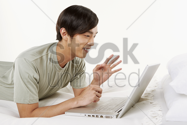 man using laptop on the bed stock photo