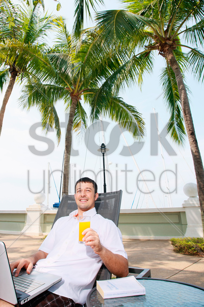 man using laptop outdoors on lounge chair stock photo