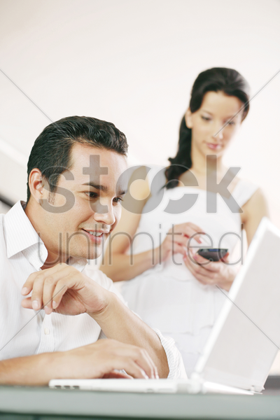 man using laptop while his girlfriend using palmtop stock photo