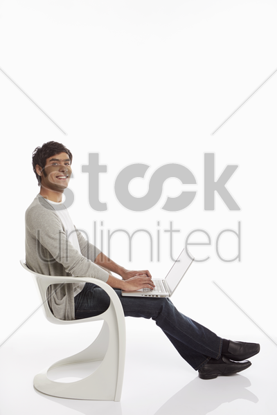 man using laptop while sitting on a chair stock photo