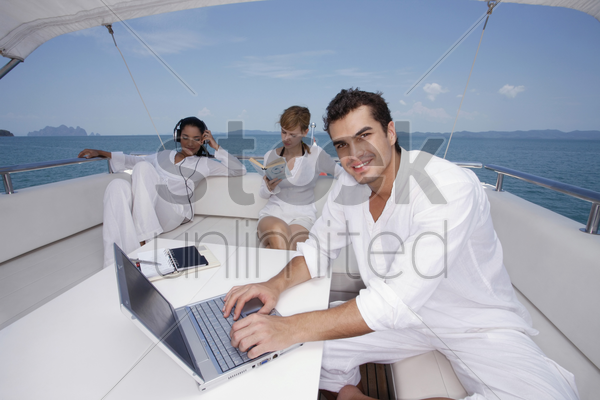 man using laptop with woman listening to music and another woman reading book stock photo